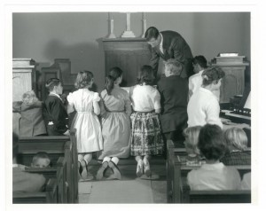 Intermountain children receive communion in Helen Piper Memorial chapel, Mills Hall (undated)